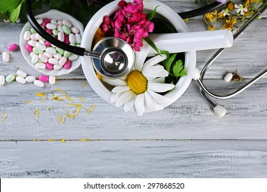 Alternative medicine herbs, berries and stethoscope on wooden table background