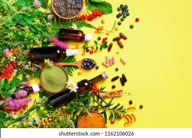 Alternative medicine. Holistic approach. Healing herbs and flowers over yellow background. Top view, copy space, flat lay. Banner