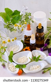 Alternative Medicine. Homeopathy. Globules, essential oils and fresh herbs on white background.
