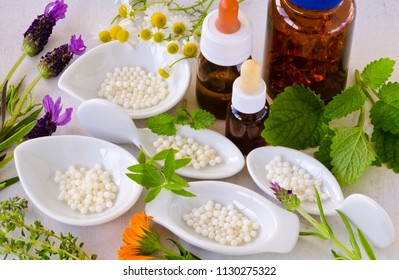 Alternative Medicine. Homeopathy. Globules and healing herbs on white background.