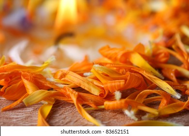 Alternative medicine -  Petals of Calendula officinalis on the edge of a perfumed candle in a half coconut shell