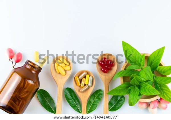 Alternative medicine, pills tablet, capsule and vitamin organic supplements good for health in wood spoon on wooden background with copy space, medicine and drug concept