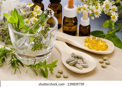 Alternative Medicine. Rosemary, mint, chamomile, thyme in a glass mortar. Essential oils and herbal supplements.