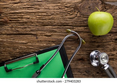 Alternative medicine - stethoscope, clipboard and green apple on wood table top view . Medical background. Concept for diet, healthcare, nutrition or medical insurance