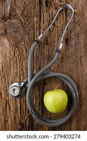 Alternative medicine - stethoscope and green apple on wood table top view . Medical background. Concept for diet, healthcare, nutrition or medical insurance