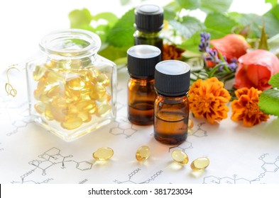 alternative medicine with supplements and essential oils on science sheet