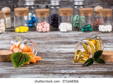 Alternative medicines with green leaves in glass containers in front versus traditional medicine in the back