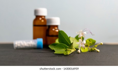 Alternative medicines - Homeopathic sugar globules and liquid substance bottles with green leaves and white flower