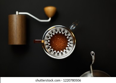 alternative method of brewing coffee. Filter with ground coffee in the funnel in focus. Left coffee grinder right teapot blurred