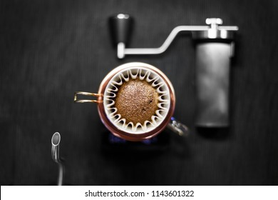 alternative method of making coffee, funnel in the foreground, coffee grinder and kettle, bloom