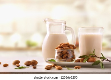 Alternative milk of almonds in a glass on a wooden table in a white kitchen. Front view. Horizontal composition.