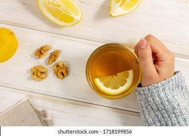 Alternative natural medicine concept, safe treatment without side effects. Cozy warm light, woman's hand dressed in grey sweater holds cup of tea with lemon on white background. Top view