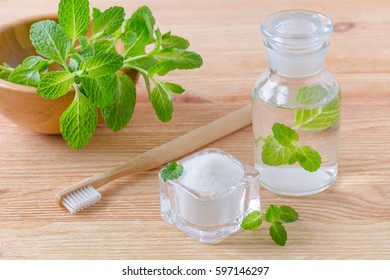 alternative natural mouthwash bottle with toothpaste xylitol, soda, salt, and wood toothbrush closeup, mint on wooden background