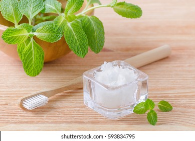 alternative natural toothpaste coconut oil and wood toothbrush closeup, mint on wooden background