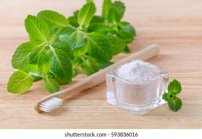 alternative natural toothpaste himalayan salt and wood toothbrush, mint on wooden background