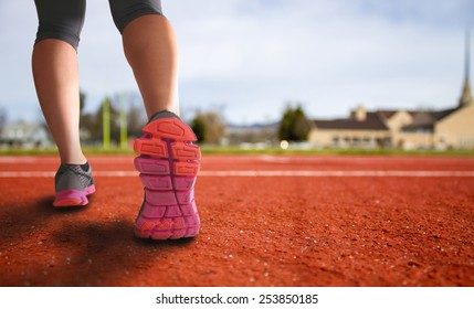 alternative perspective of woman prepping to run a track for exercise with church in the background and field in the city with an instagram filter (shallow depth of field)