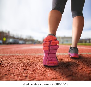 alternative perspective of woman running on a track mid-stride with a drama filter (shallow depth of field)