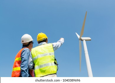 Alternative Power or Renewable Energy Technology Project Development Concept, Engineer and Architect discuss over Digital Wireless Tablet and Clipboard while working at Wind Turbine Power Generator To