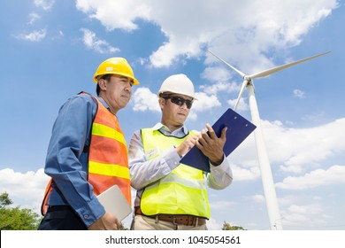 Alternative Power or Renewable Energy Technology Project Development Concept, Engineer and Architect discuss Digital Wireless Tablet and Clipboard while working at Wind Turbine Power Generator To