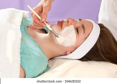 Alternative practitioner performing a chemical face peel on a young female patient