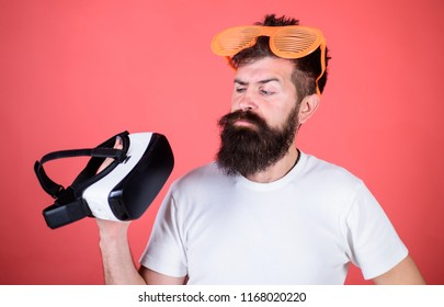 Alternative reality. Man bearded hipster with virtual reality headset and louvered sunglasses red background. Which glasses choose louvered or virtual. Man making decision what choose real or virtual.