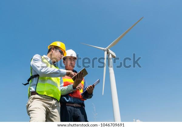 Concepto de desarrollo de proyectos de tecnología de energía alternativa o renovable, ingeniero y arquitecto discuten sobre tableta y portapapeles inalámbricos digitales mientras trabajan en el Generador de energía de turbina eólica a