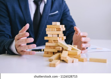 Alternative risk concept, plan and strategy in business protect with balance wooden stack with hand control risk shape.