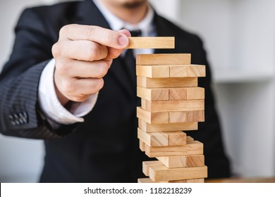 Alternative risk concept, plan and strategy in business, Risk To Make Business Growth Concept With Wooden Blocks, Images of hand of business people placing and pulling wood block on the tower.