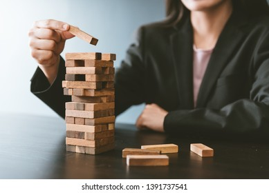 Alternative risk concept, plan and strategy in business,businesswoman playing the wood game, hands of businesswoman  placing wood block on the tower.