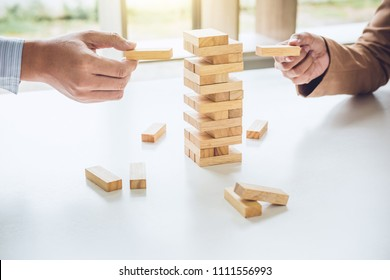 Alternative risk plan and strategy in business, Young intelligent business team playing the wood game, hands of executive cooperation placing wood block on the tower, Collaborative management.