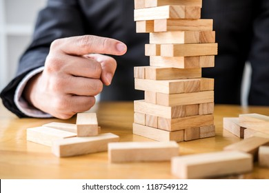Alternative risk plan and strategy to growth profit in business, Young intelligent businessman playing the wood game, hands of executive placing wood block on the tower.
