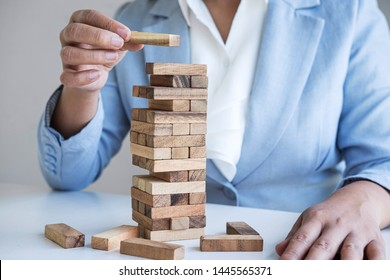 Alternative Risk and Strategy in Business, Hand of intelligent business woman gambling placing making wooden block hierarchy on the tower to planning and development to successful.