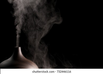 Alternative spa therapy device. Electric essential oil aromatherapy diffuser producing vapor. Close up of atomizer in use against black background.