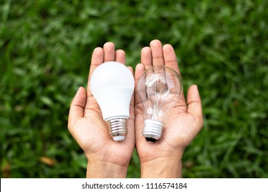 Alternative technology concept . Hands holding LED Bulb and Fluorescent bulb comparing in hands . copy space for text .