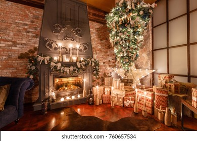 alternative tree upside down on the ceiling. Winter home decor. Modern loft interior with fireplace and brick wall
