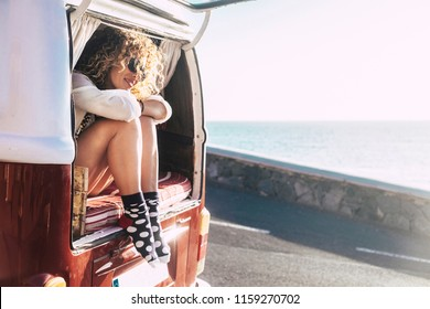 alternative way of travel and enjoy the world. discover new places and live with ocean view from the window. happy beautiful female sitting outside a classic van and looking at the sea. relax
