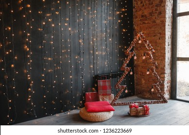 Alternative wooden christmas tree. A handmade New Year tree with light bulb on garland bokeh black background. Loft interior. Copy space