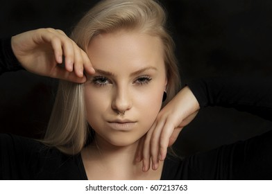 Alternative young female model with blonde hair and piercings in her nose on a black background.