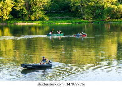 Althom, Pennsylvania, USA 8/10/2019 A boat and kayaks on the Allegheny river in Warren county on a summer day