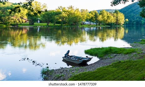 Althom, Pennsylvania, USA 8/10/2019 A fishing boat tied up to the shore on the Allegheny river in Warren county in summertime