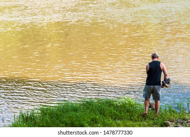 Althom, Pennsylvania, USA 8/10/2019 A man using a weed whacker to to trim grass along the Allegheny river in Warren county in summertime