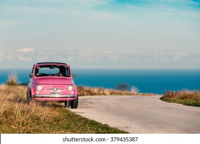 ALTIDONA, ITALY - FEBRUARY 20, 2016: Old pink Fiat Nuova 500 city car. Produced by the Italian manufacturer Fiat between 1957 and 1975.