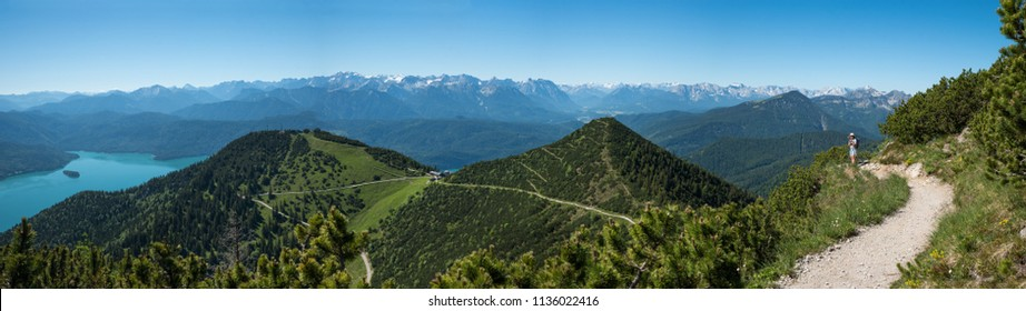 altitude walkway herzogstand mountain. young woman makes a selfie. bavarian panorama landscape
