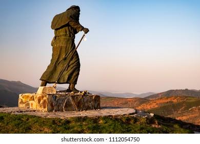 Alto de San Roque - 2 km to Liñares at sunrise, the statue of a pilgrim against the storm.