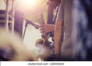 Alto sax musical instrument closeup,jazz musician playing outdoor concert