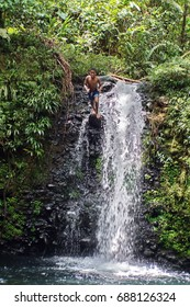 ALTO TAMBO, ECUADOR - CIRCA JULY 2017: Local children jumping into a pond beneath a waterfall in the jungle outside of town