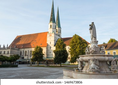 """Altotting, Bayern / Germany - July 17 2019: Early morning sun lighting the church at pilgrimage town with """"Marienbrunnen"""" fountain"""