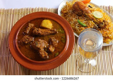 Alu gosht and chicken biryani with glass of water, Traditional indian dish, Famous pakistani food, Ramadan iftar meal, Diwali or christmas party dinner, Chicken Qorma for easter or birthday party