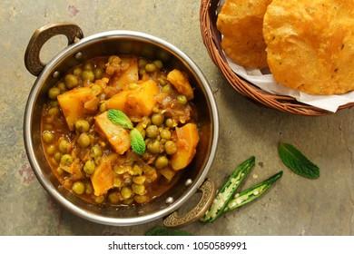 Alu Matar ( Aloo Mutter) served with Masala Puri or Poori / Indian Potatoes Pes curry