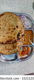 Alu paratha - North Indian Potato stuffed bread served in a basket with chickpeas curry &  mango pickle .